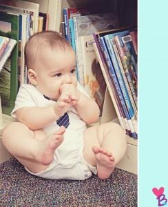 Happy baby among bookshelves
