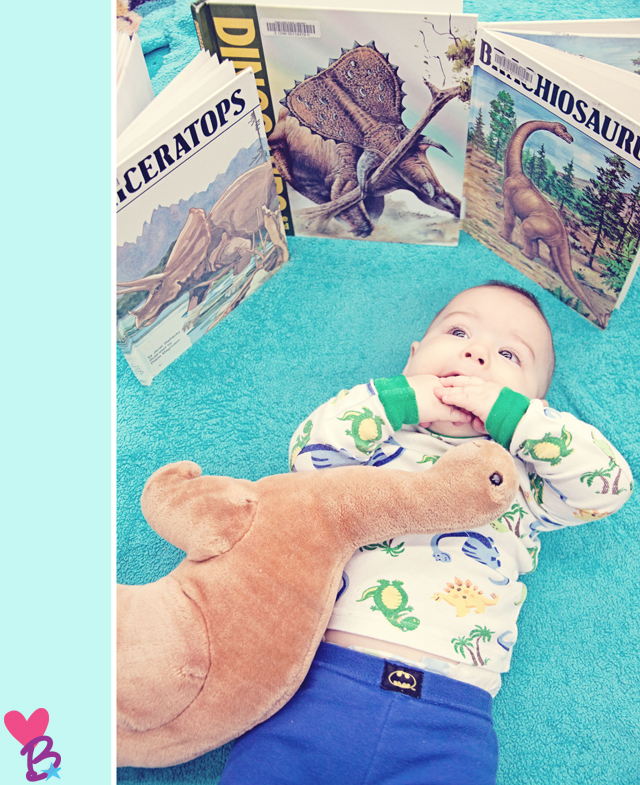 Baby in dinosaur pjs surrounded by dinosaur books and toy