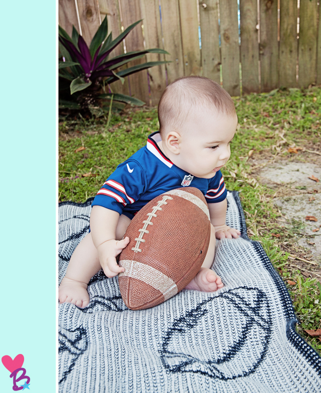 Baby holdiong football on blanket