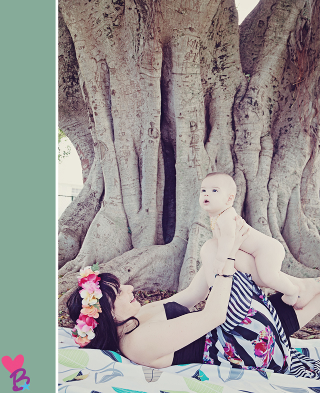 Mom laying down with naked baby under tree