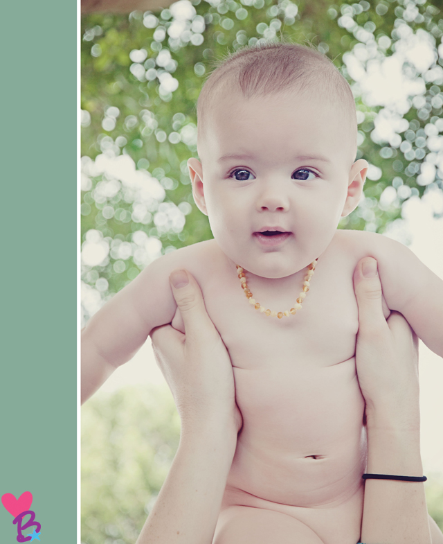 Naked baby with amber teething necklace under tree
