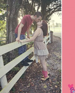 Engagement photo kiss on fence with girl on tiptoes