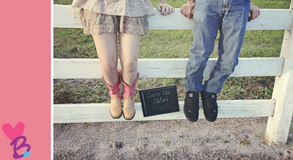 Save the date engagement photo with girl's pink cowboy boots and boy's sneakers next to sign
