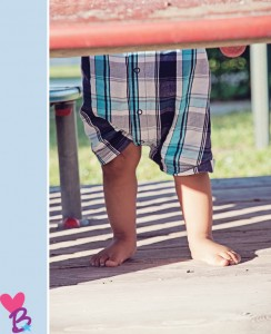 Park photo shoot baby on playground standing feet only