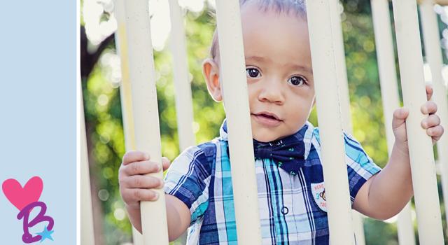 Baby at parl behind fence close-up