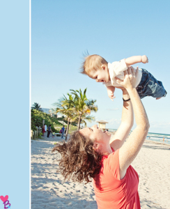 Beach shoot mom holding baby up in air
